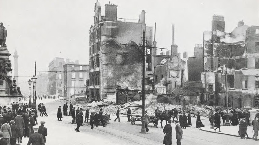 Black and white historic photo showing destroyed buildings and rubble on Sackville St in Dublin