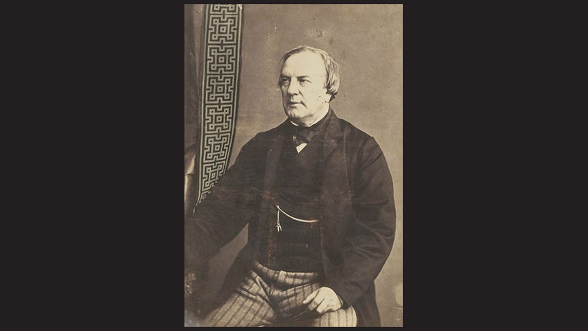 black background with sepia photo of seated man with black jacket, watch chain and striped trousers
