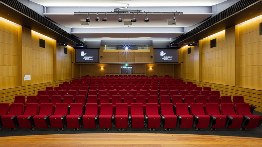 Theatrette with rows of red seating, stage and lighting