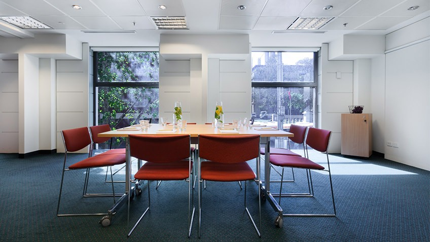 seminar room with central table and chairs, windows and natural light