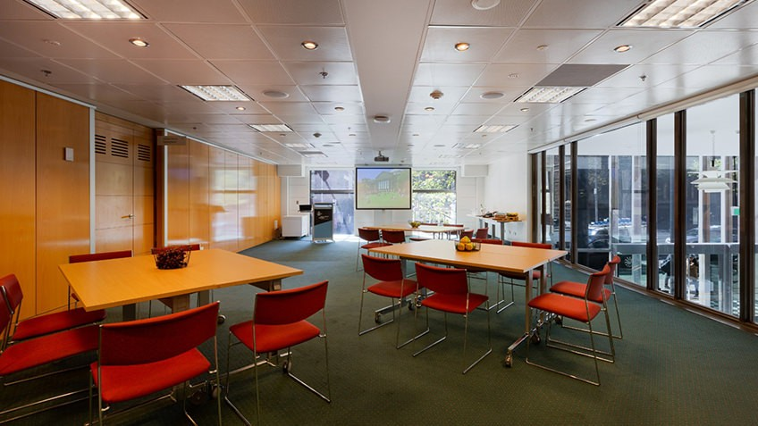 seminar room with natural light, wooden tables and red seats