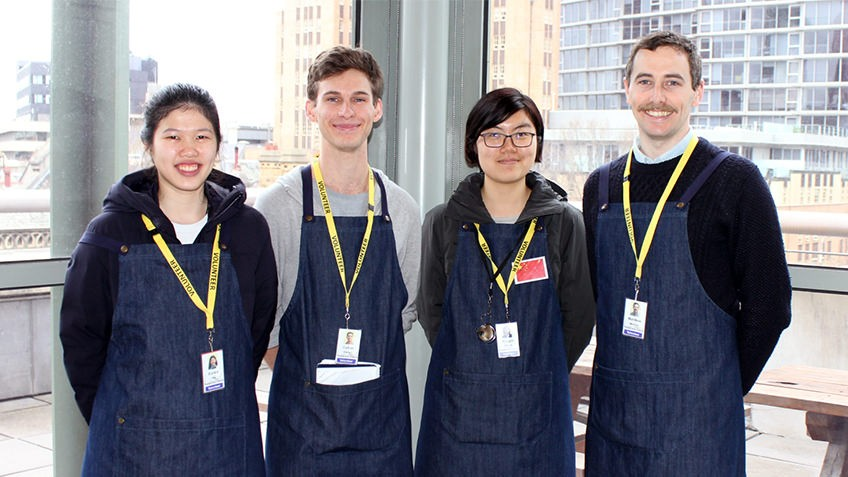 four young people smiling on a rooftop balcony wearing identity lanyards