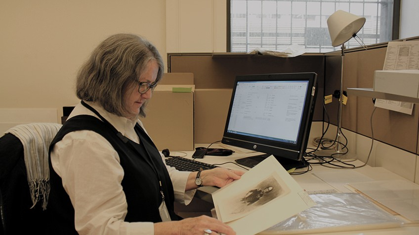 A woman at a desk looks down at a print of a man's portrait that she holds