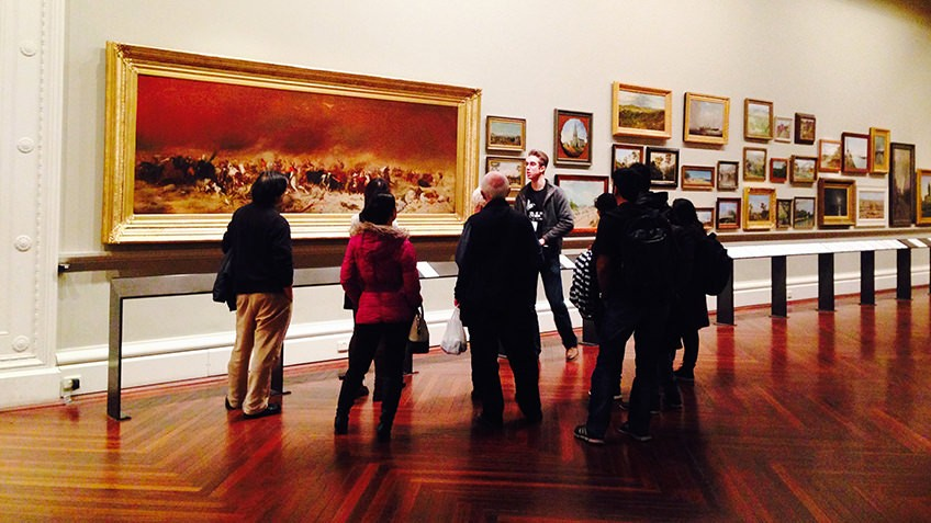 A man talks to a group of visitors in an art gallery