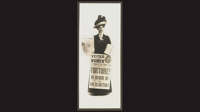 black background with Edwardian woman wearing hat and holding placard with Votes for Women