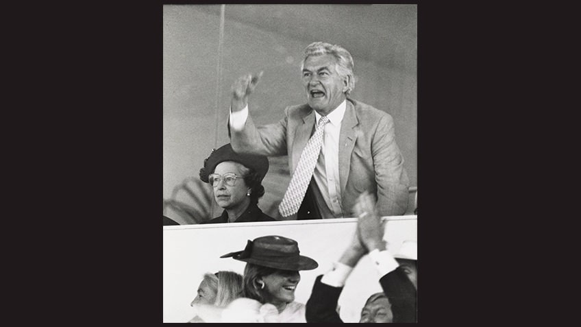black and white photo of victorious Bob Hawke and frowning Queen Elizabeth
