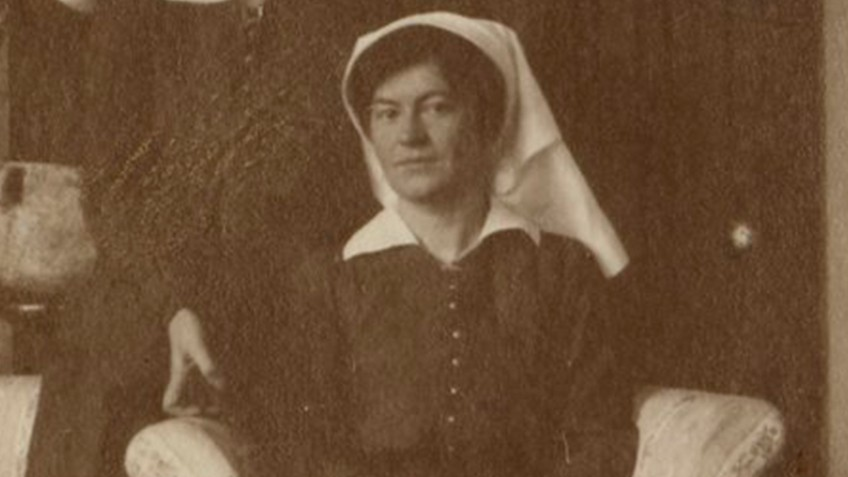 Black and white photo of two nurses in a sitting room in Egypt during WWI, one seated in an armchair, the other standing beside her, both nurses wearing dark outfits with white collars and veils