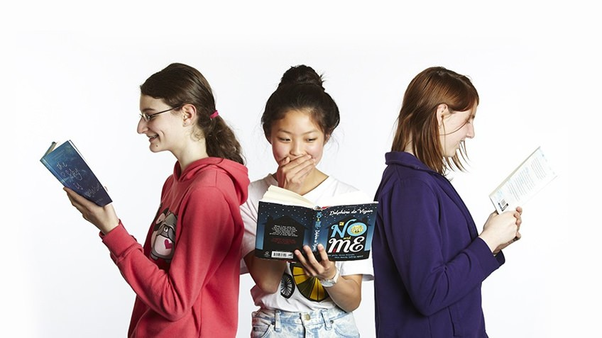 Photograph of three teenagers reading books