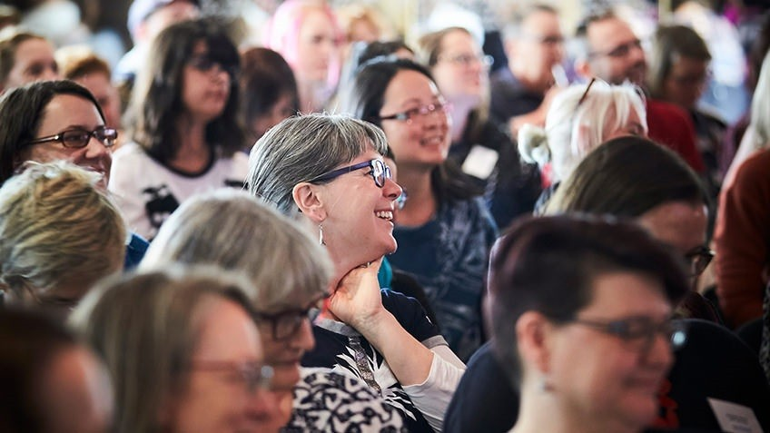 A laughing woman stands out in an audience of other women