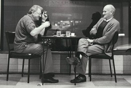 A black and white image of two men sitting outside a coffee shop sipping drinks and smoking