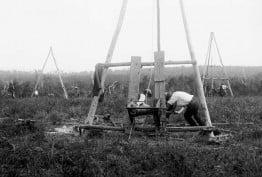 1920-1925 glass negative image. Early bore holes, testing coal. Shows men operation mining windlasses