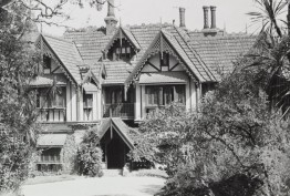 Black and white exterior photo by John T Collins of Tay Creggan in Hawthorn, a double-storey residence with imitation half-timbering, decorative timber barge-boards, steep gables and a tiled roof