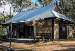stone bush cottage with corrugated-iron roof surrounded by gum trees and statues