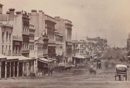 Photograph of Collins Street from Swanston Street, Melbourne, ca. 1872. Shows buildings including Staffordshire House and W. H. Rocke & Co. Several horse and carriages can be seen along the street.
