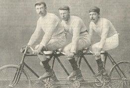 Sepia image of three Victorian-era men riding a tandem bicycle