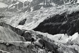 Black and white photo of small group of mountaineers ascending snow covered alps, possibly in Switzerland, carrying walking sticks or mountain poles