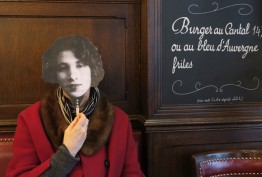 french cafe with blackboard menu and woman in red coat holding up the black and white facemask of a woman