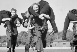 black and white photo of three uniformed women on an oval carrying male dummies