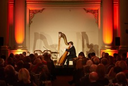 Photo of a harpist playing in front of an audience in Queen's Hall