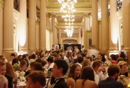 Colour photo of dining event crowd in front of the columns and lights of Queen's Hall