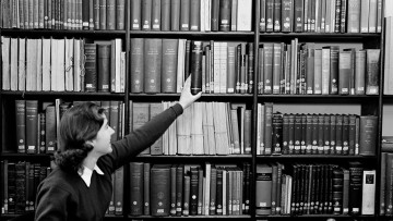 A woman reaches up to a bookshelf to take hold of a book