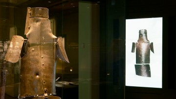 Ned Kelly's armour spotlit against black background next to slide image of armour on white background