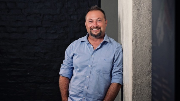 Man leaning on a wall and smiling at the camera
