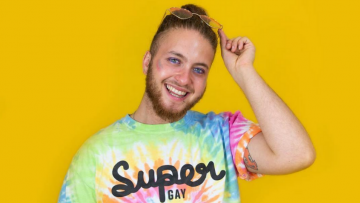 Headshot in front of a yellow background with a rainbow shirt
