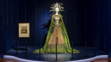 A mannequin on display wears a majestic cloak and a striking headdress