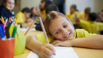 A girl smiles as she writes with pencil on paper