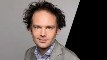Headshot of Erik Jensen on grey and black background
