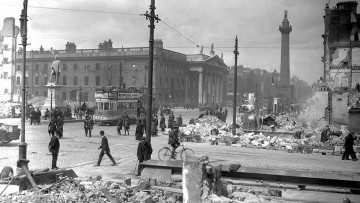 Black and white photo of an intersection with bombed buildings and rubble