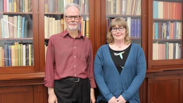 Des Cowley and Anna Welch exhibition curators in front of bookcases