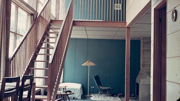 modernist house interior with wooden staircase to mezzanine level from lounge
