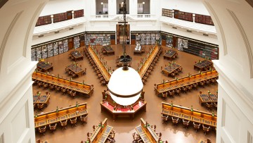 Photo of desks in the La Trobe reading room through an archway with a light globe in the centre