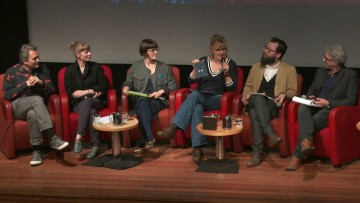 six people in conversation seated on a stage