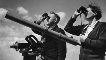 Black and white image of man and woman looking at sky through binoculars.