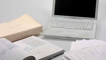 Photo of a laptop and some printed manuscripts