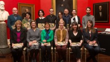2015 Creative Fellows group photographed against red walls and paintings of Red Rotunda