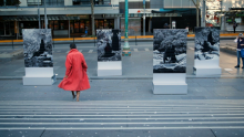Woman with red dress in front of artworks at State Library Victoria