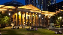 Library facade forecourt and lawns at night