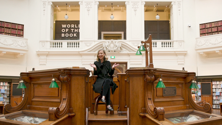 A smiling woman in a black dress sits in a timber dais in a large, elegant room