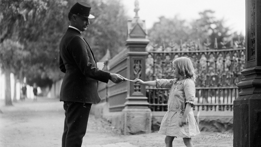 A man in uniform hands a letter to a small girl