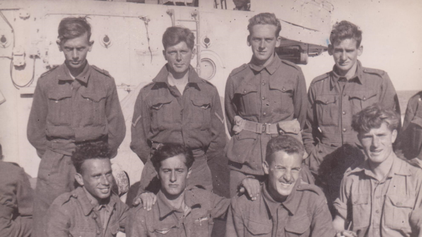 A black and white photo of a group of soldiers standing together on the HMS Kimberley.