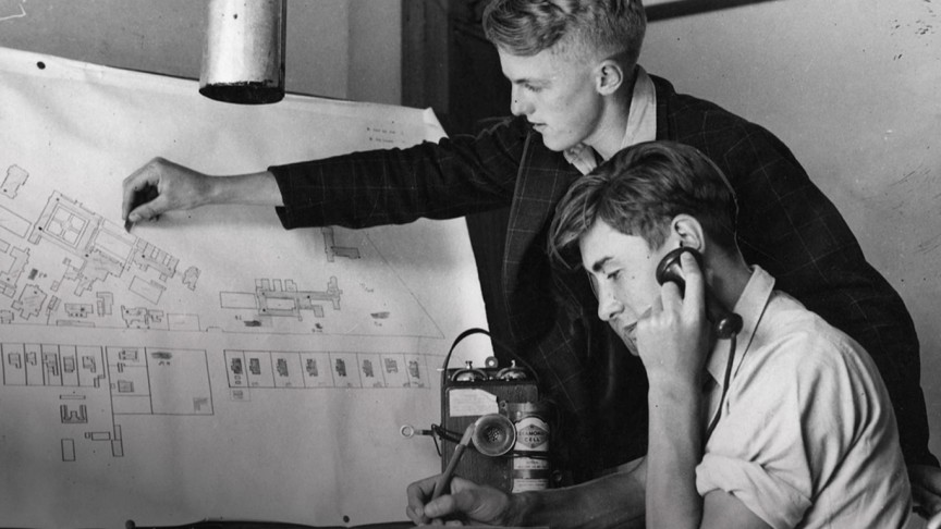 Two young men scrutinise a large map