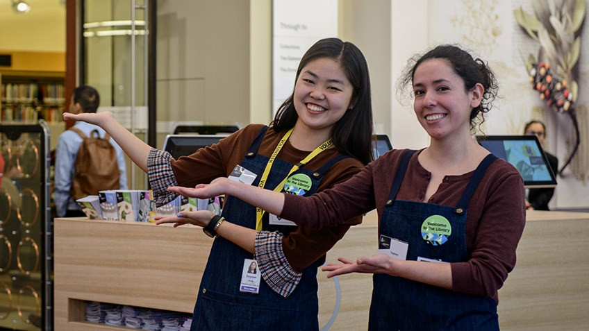 two young women smiling and welcoming visitors to the library