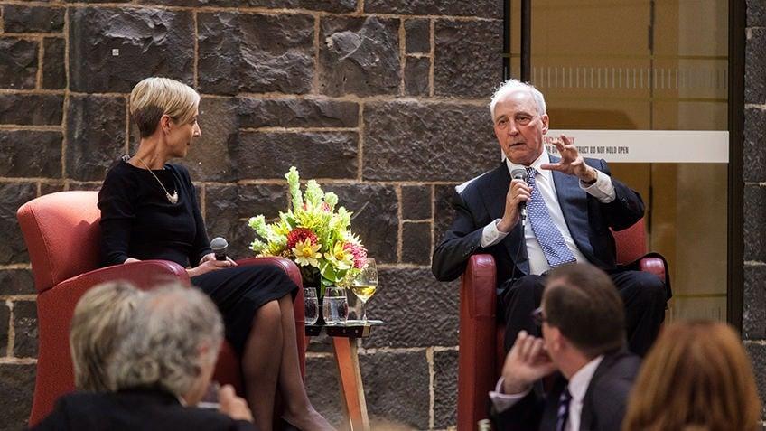 A woman and a man talk on a podium in a bluestone room