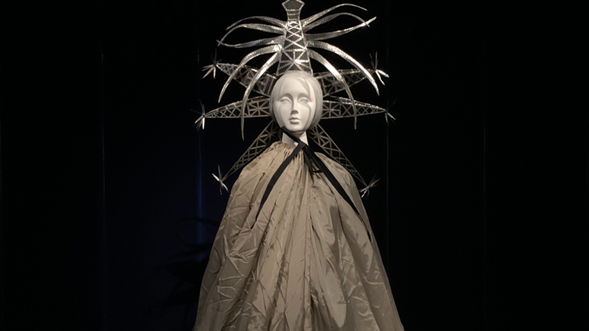 A mannequin wears a striking headress and a floor-length cloak