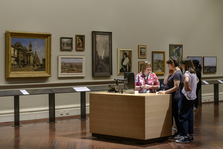 A smiling librarian helps two people in an art gallery