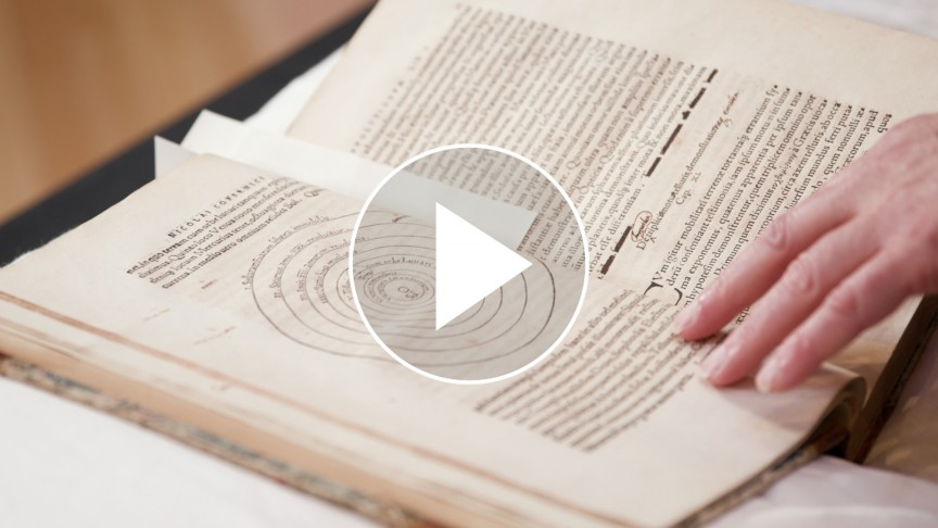 An open book with a play button on top